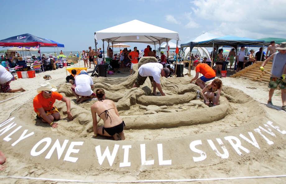 "A team works on their sand sculpture themed ""Only One Will Survive"" during the 26th annual AIA SandCastle Competition on Galveston's East Beach Saturday, June 2, 2012, in Galveston. The event brought out over 60 teams with the winner receiving the Gold Bucket Award. Photo: Cody Duty, Houston Chronicle / © 2011 Houston Chronicle"