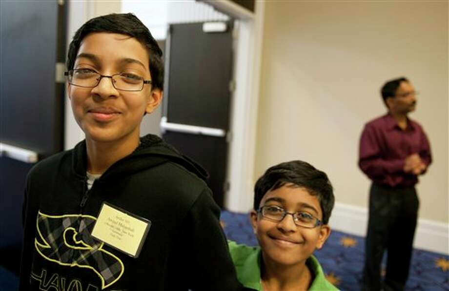 Scripps National Spelling Bee contestant Arvind Mahankali, 13, of Bayside Hills, N.Y., left, departs with his younger brother Srinath, 9, after completing the Preliminaries Test phase of the Bee in Oxon Hill, Md., Tuesday, May 28, 2013. Arvind finished 3rd in the Bee last year. Spellers arrived Tuesday morning to take a 45-minute computer test that probes their knowledge of both spelling and vocabulary. The results will be combined with Wednesday's on-stage round to determine which spellers will advance to the semifinals Thursday. Photo: Cliff Owen, AP / FR170079 AP