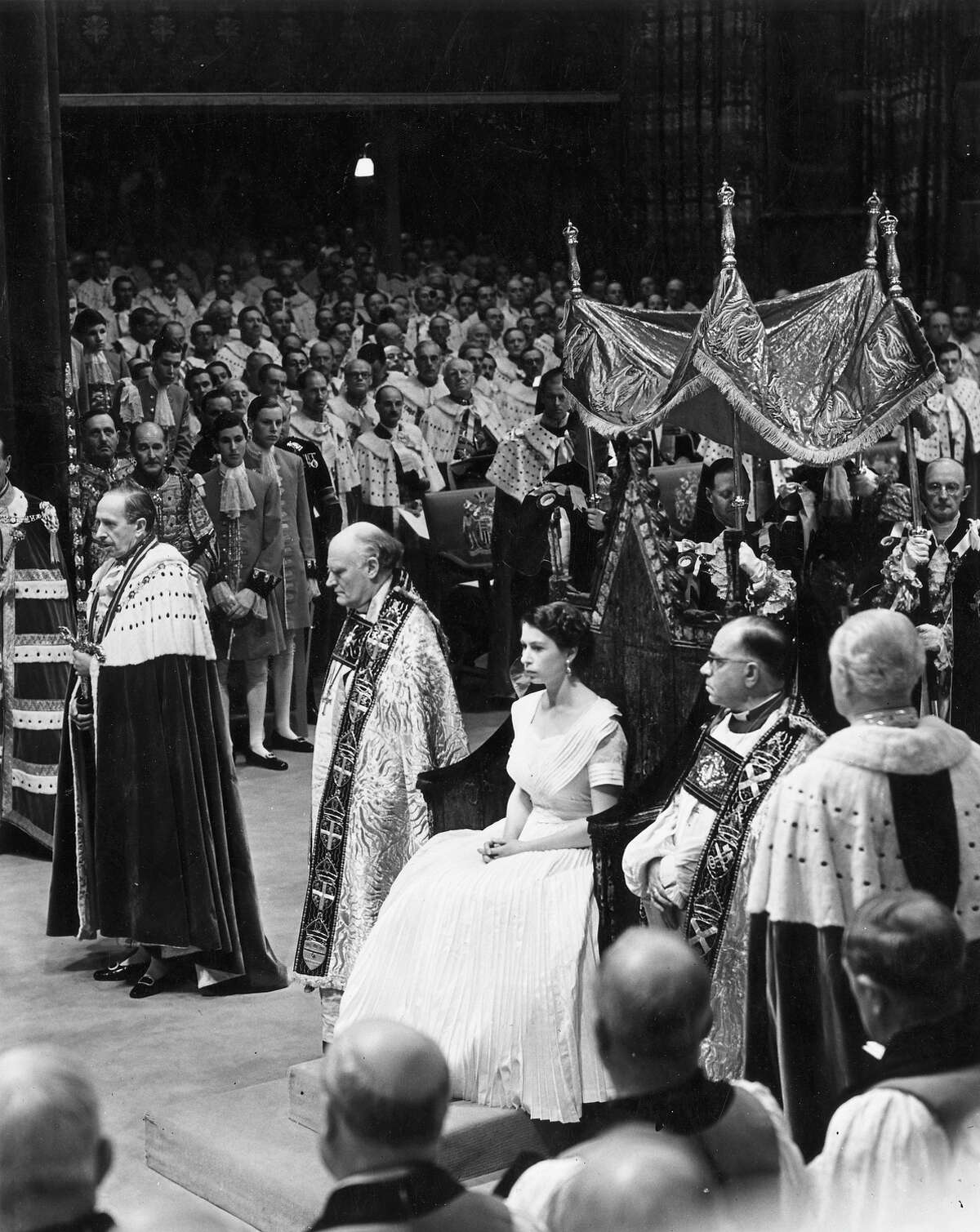 Wearing a simple white dress and surrounded by dignitaries, Queen Elizabeth II sits in St Edward's Chair at her coronation ceremony before she is appointed. Behind her four Knights of the Garter hold the canopy that will be held above her head.