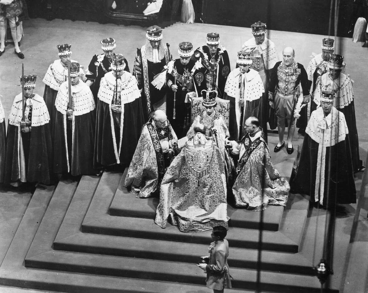 Queen Elizabeth II seated on a throne in Westminster Abbey attended by dignitaries whilst Bishops pay homage to her.