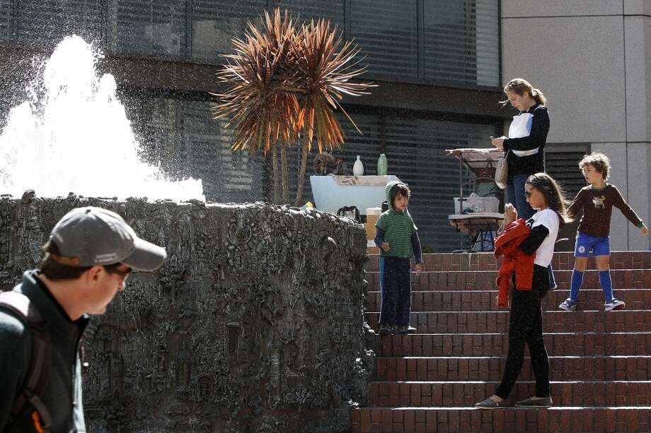 Krystal Elam (right, white shirt) from San Diego takes pictures of Ruth Asawa's 'Hyatt on Union Square Fountain', 1973, at the triangular plaza behind the Levi's store in San Francisco, Calif., on Friday, May 24, 2013.  Asawa made the model for this bronze fountain using baker's clay depicting San Francisco, with approximately 250 friends and school children helping to make it by contributing self-portraits, cars, buildings, and various San Francisco landmarks. The Levi store will soon be replaced by a new Apple Store where plans apparently seem to remove the fountain.