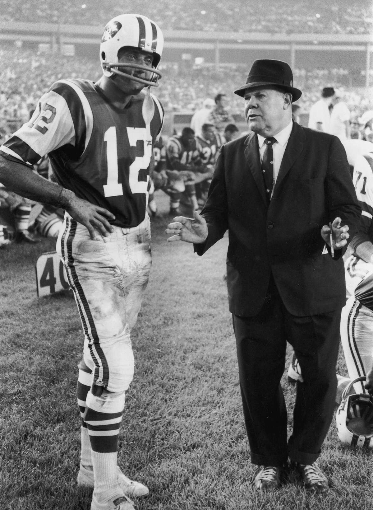New York Jets quarterback Joe Namath standing with his hands on his hips while listening to coach Weeb Ewbank during a game in Shea Stadium, Flushing, New York, fall season, 1965.