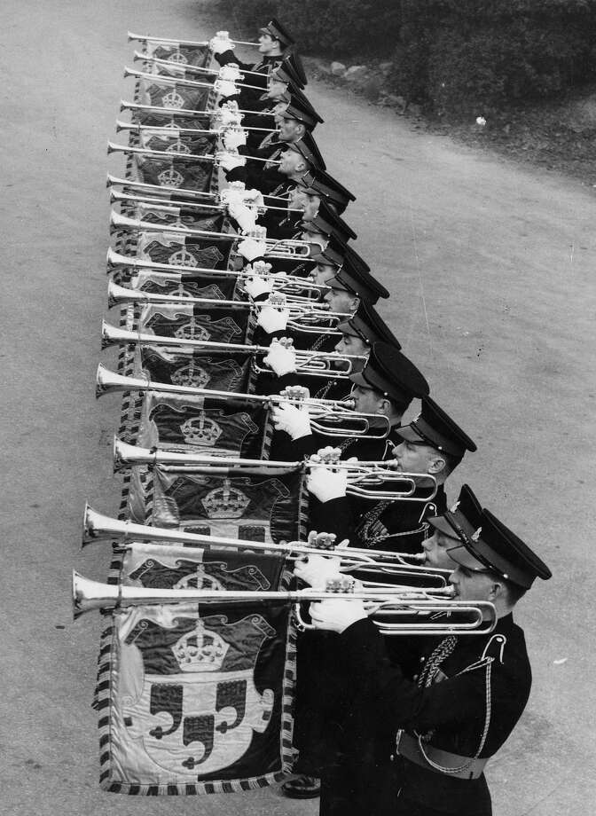 23rd March 1953:  A line of trumpeters outside Kneller Hall, the Royal Military School of Music, practice their instruments before the Coronation of Queen Elizabeth II. Hanging from their trumpets are the school's heraldic bannerets. Photo: Douglas Miller, Getty Images / Hulton Archive