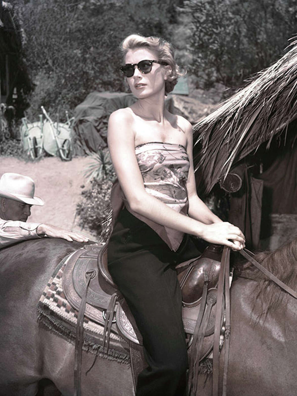 Riding a horse on set, c. 1953.Kelly's outfit equation couldn't be simpler: Sunglasses + scarf as top + black pants = relaxed glamour.