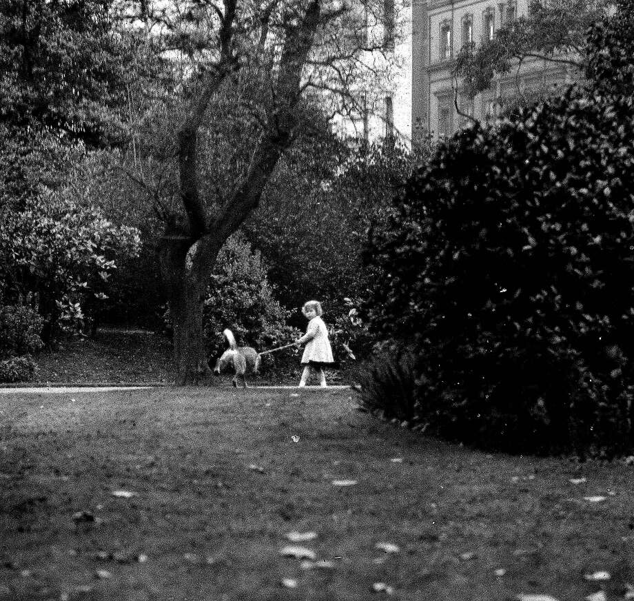 """Princess Elizabeth holds onto one of her pet dogs as it """"spends a penny,"""" in one of London's parks in 1930. Photo: Popperfoto, Popperfoto/Getty Images / Popperfoto"""