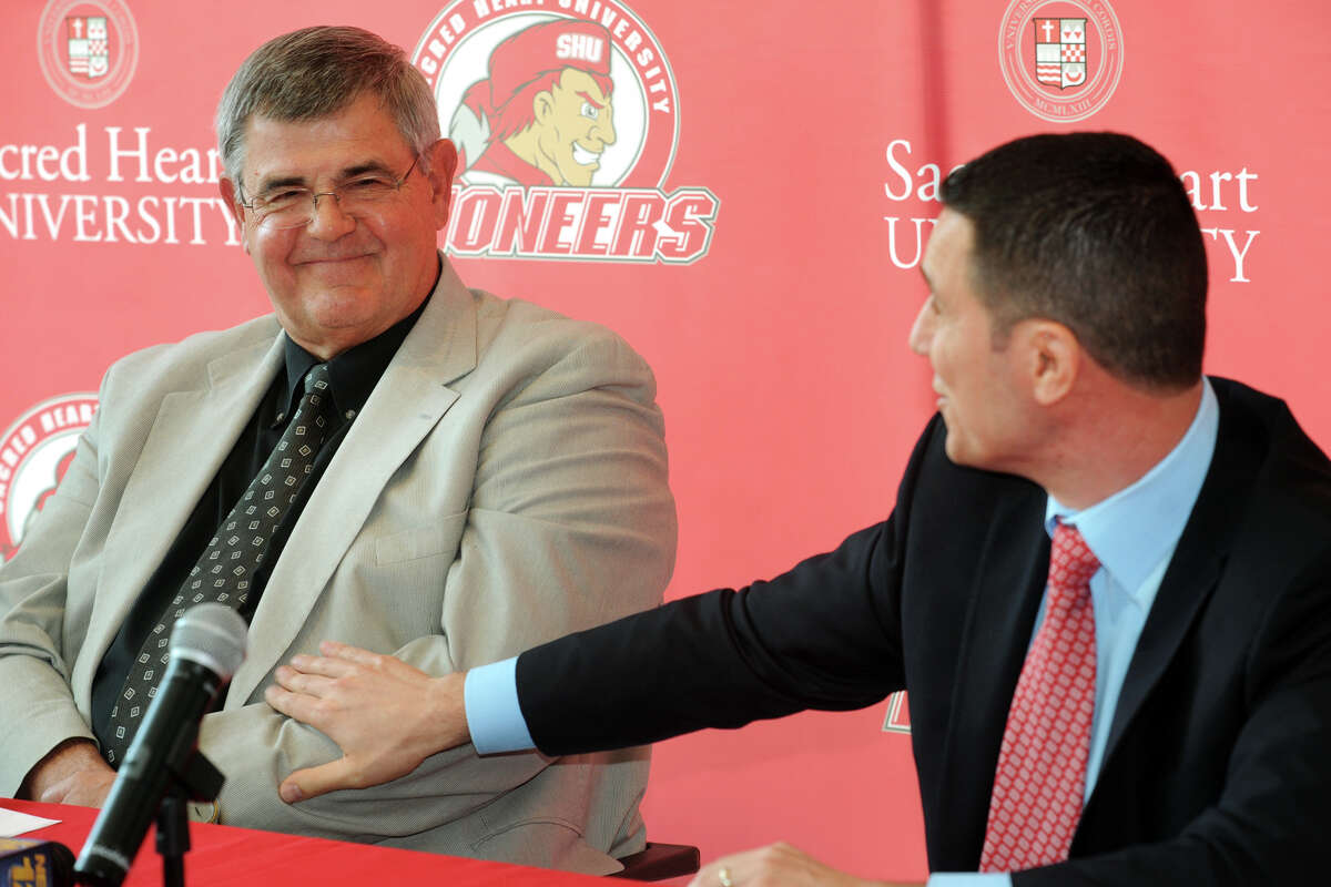 Former Sacred Heart University men's basketball coach Dave Bike, left, recieves a warm compliment from new coach, Anthony Latina, during a press confernece in the McMahon Center on campus in Fairfield, Conn., May 30th, 2013.