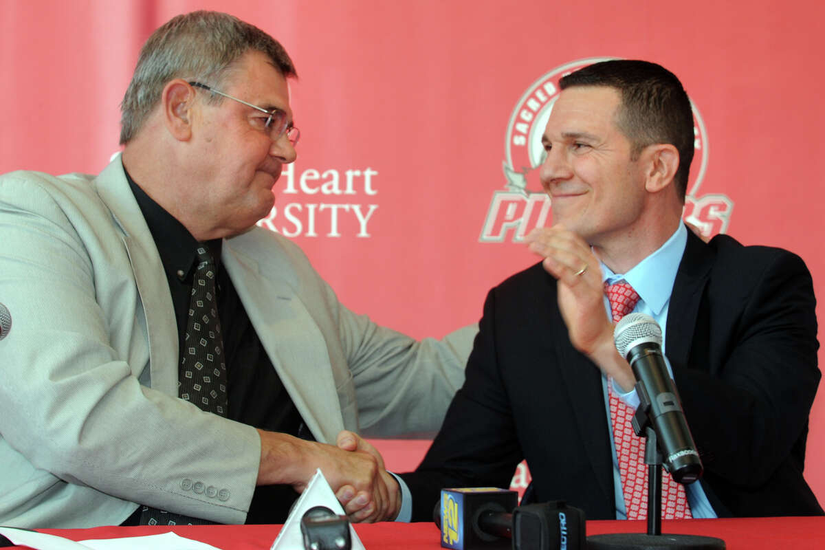 Former Sacred Heart University men's basketball coach Dave Bike, left, shakes hands with new coach, Anthony Latina, during a press confernece in the McMahon Center on campus in Fairfield, Conn., May 30th, 2013.