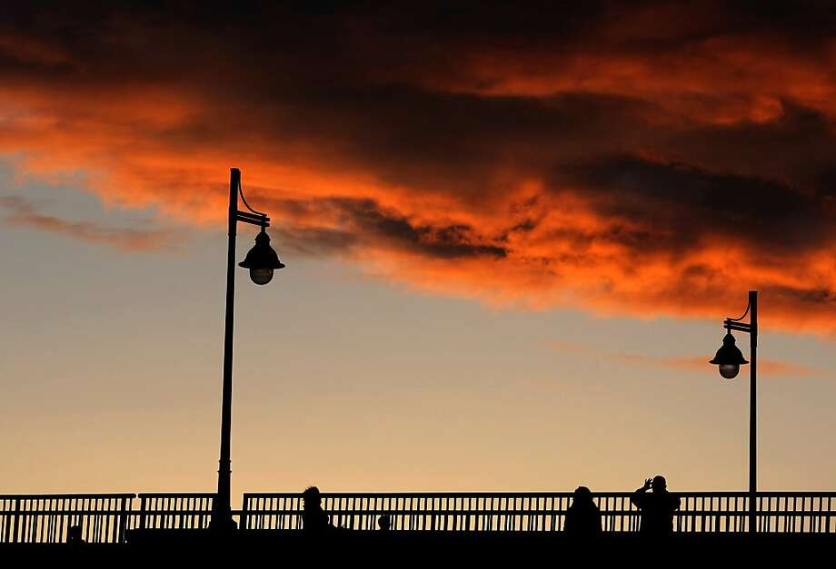 Sunset admirers stop to take photos from the Manette Bridge in Bremerton, Wash. Photo: Larry Steagall, Associated Press