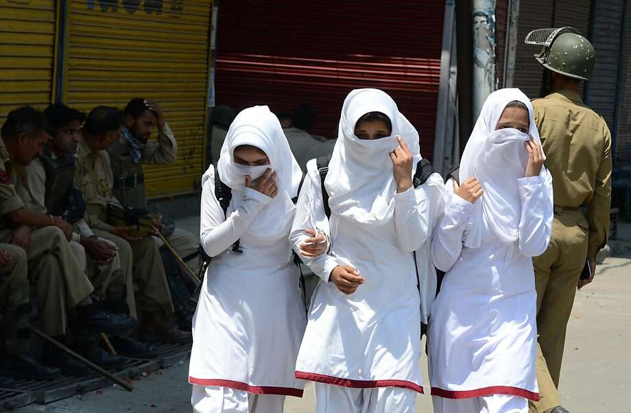 Tense days in Kashmir:Kashmiri schoolgirls cover their faces as they walk past Indian policemen taking a break from the heat while patrolling Srinagar. Much of Kashmir has been under curfew following demonstrations and strikes protesting the recent hanging of Mohammed Afzal Guru for plotting the attacks on the Indian parliament in 2001. Photo: Tauseef Mustafa, AFP/Getty Images