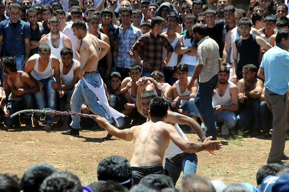 Trial by scourge: Young Kurds whip each other during one-on-one combat to prove their courage at Dicle in Diyarbakir, Turkey. The fights, part of the so-called Whip Fest, are a thousand-year-old tradition that villagers believe will increase their harvest. The thick rope whips, soaked in water for a day before they are used, often leave deep scars on the young men. Photo: Mehmet Engin, AFP/Getty Images