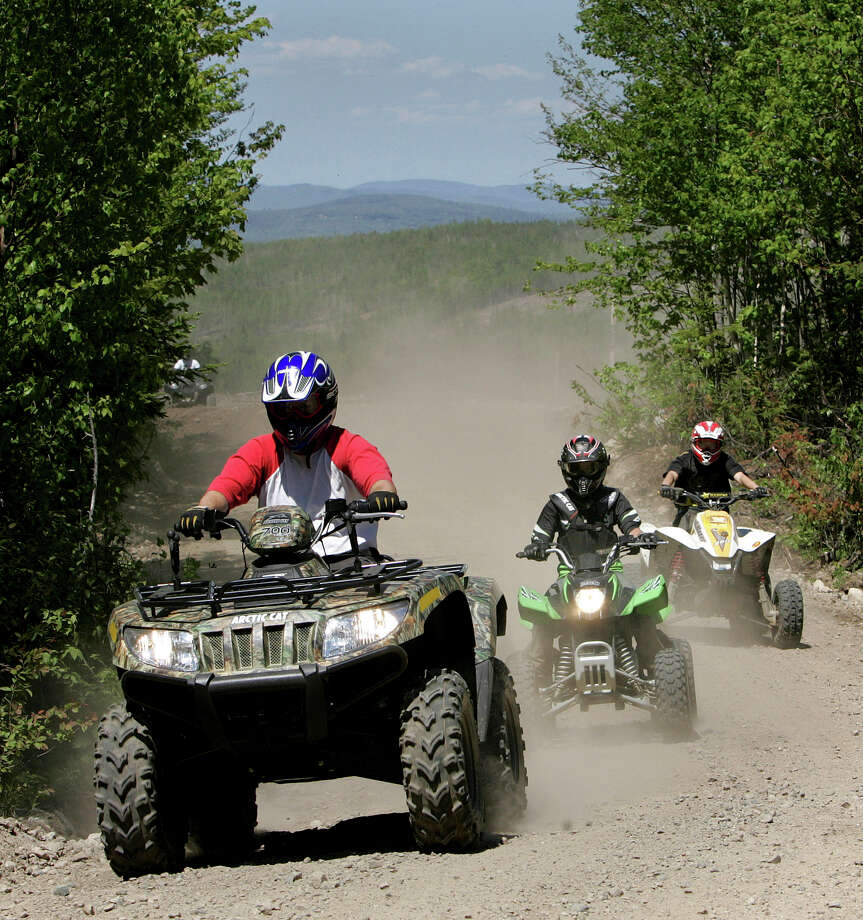 "FILE -  In this Sunday, May 23, 2010 file photo, Jude Stohl leads Leigha Cicchetto and his son Ethan Stohl on a ride through Jericho Park's trail system in Berlin, N.H. In New Hampshire, a new interconnected all-terrain vehicle trail system dubbed ""Ride the Wilds"" will officially open June 15, 2013, capping years of work by more than a dozen off-road vehicle clubs who worked with state agencies and local communities to link 1,000 miles of trails across Coos County. (AP Photo/Jim Cole, File) Photo: Jim Cole"