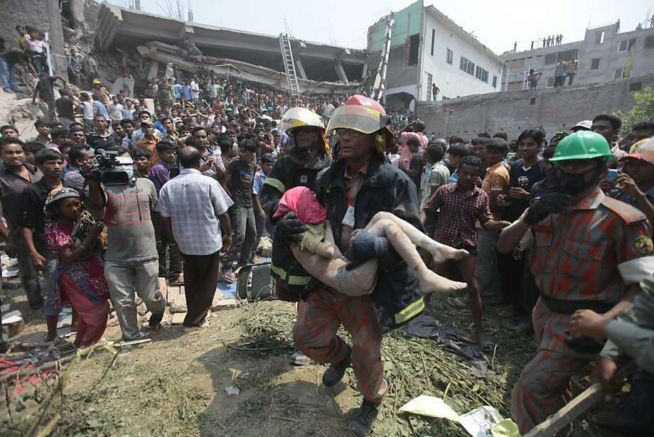 Rescue workers carry a young victim's body after an eight-story building housing several garment factories collapsed in Savar, near Dhaka, Bangladesh, in April. The death toll from the disaster reached 1,130 workers. Photo: A.M. Ahad, Associated Press