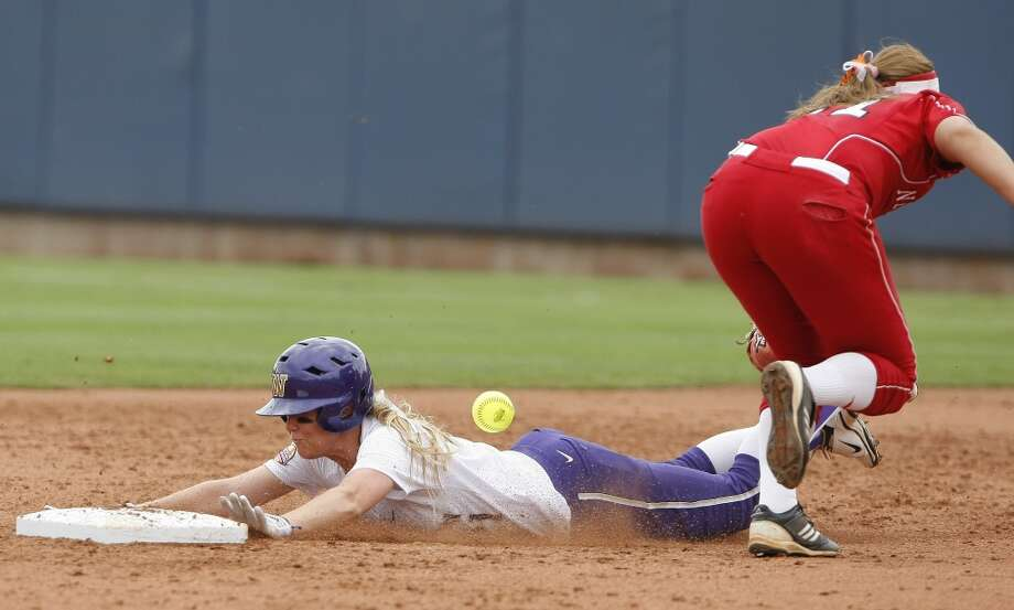 ADDS INFO - Washington's Victoria Hayward slides safely into second as Nebraska's Sammie Nolan misses the ball during the third inning of a Women's College World Series NCAA softball tournament game in Oklahoma City, Thursday, May 30, 2013. Hawyard stole second and advanced to third on a throwing error by Nebraska. (AP Photo/Alonzo Adams)