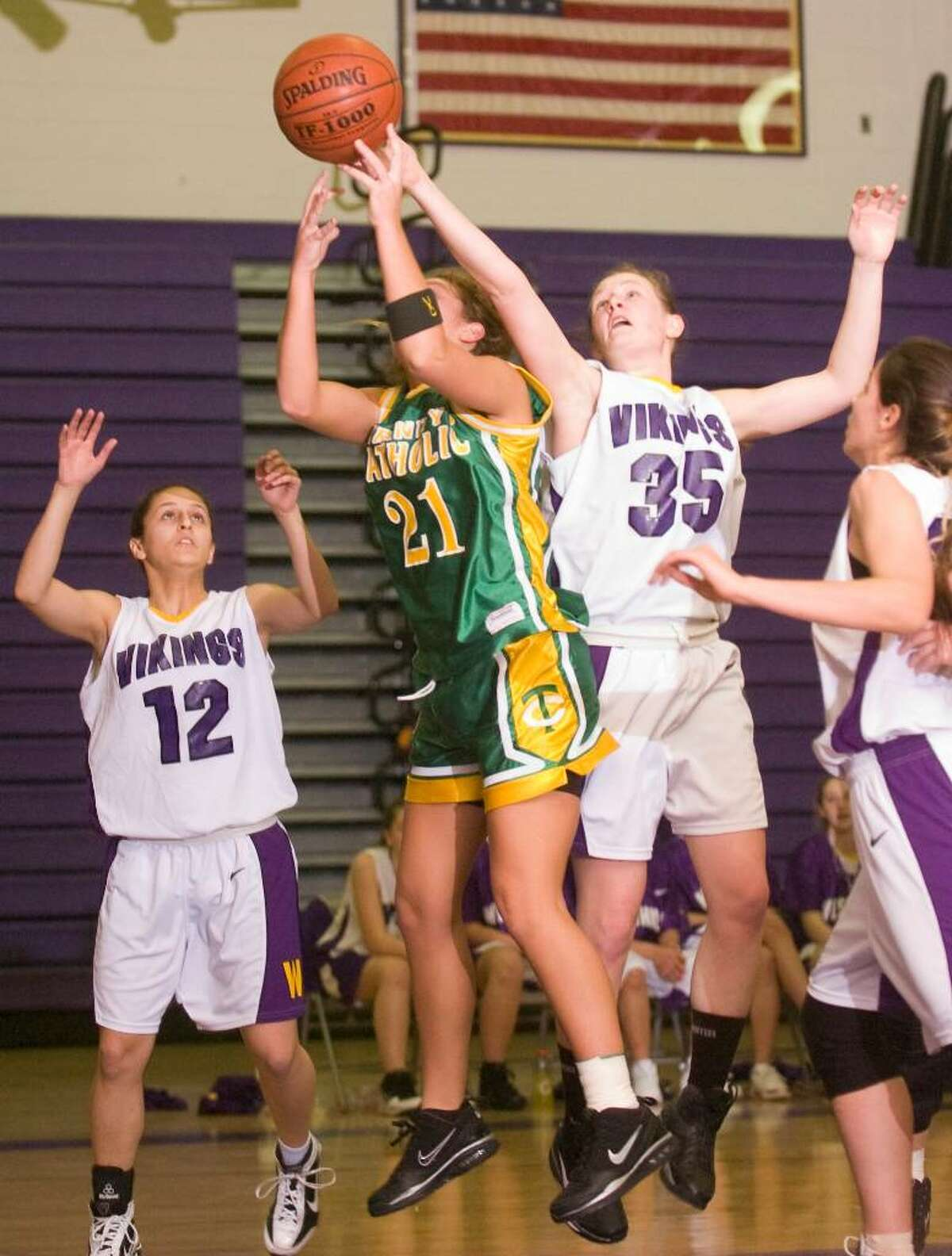 Westhill's Ann Hawthorn, right, tips a rebound away from Trinity Catholic's Clare O'Leary, center, during and FCIAC girls basketball game at Westhill High School in Stamford, Conn. on Tuesday, Jan. 12, 2010.