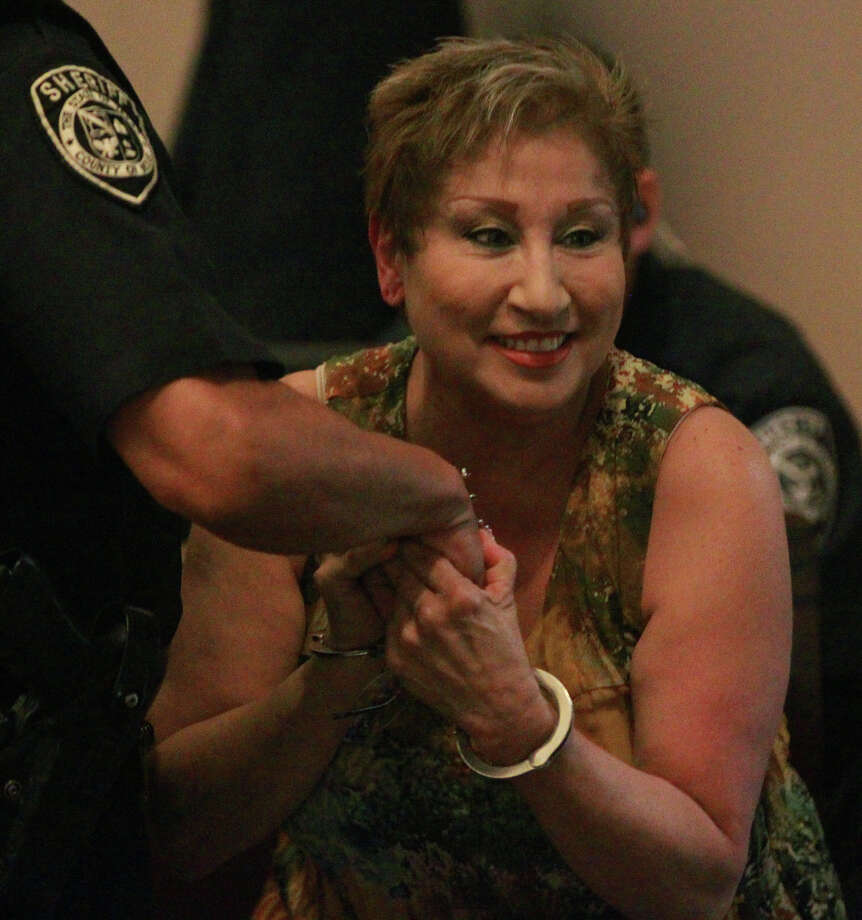 Silvia Gallegos Neira, 58, is helped up after being handcuffed Thursday May 30, 2013 in the 186th District Court after being sentenced to eight years in prison. The former South San Antonio Independent School District secretary who collected and deposited football game ticket revenue was sentenced for skimming more than $22,000 of the proceeds for herself. Photo: JOHN DAVENPORT, SAN ANTONIO EXPRESS-NEWS / ©San Antonio Express-News