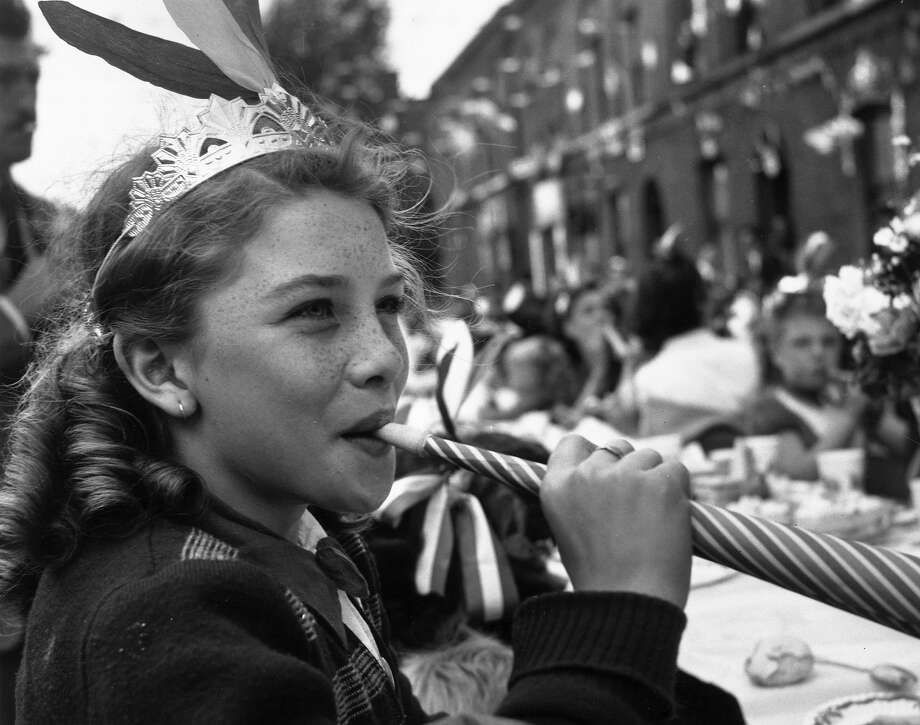 A girl blowing a paper whistle at a party in Morpeth Street in London's East End during Queen Elizabeth II's Coronation celebrations. Photo: John Chillingworth, Getty Images / 2006 Getty Images