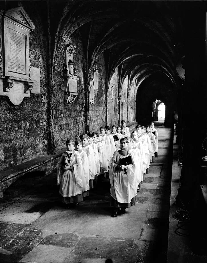 Preparations for the Coronation of Queen Elizabeth II, In their white surplices, ruffs and scarlet cassocks with mortarboards clasped under their arms, Westminster Choir Boys pass through the cloisters on their way from the Song School to the Abbey. Photo: Popperfoto, Popperfoto/Getty Images / Popperfoto