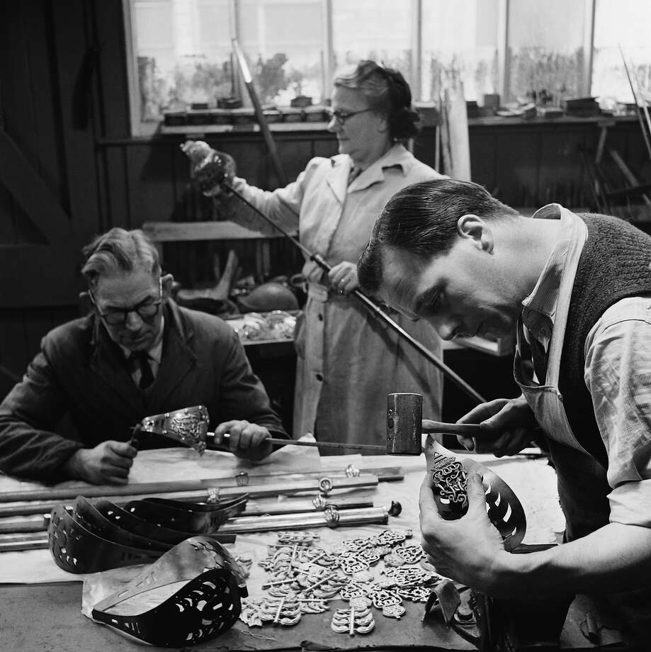 Foreman Herbert Macnab assembles a Lifeguard's State sword, ready for the Coronation of Queen Elizabeth II, 1953. Mrs Fry examines the finished product and Eric Silverthorne rivets the Lifeguards' crest onto the hilt. Photo: Paul Popper/Popperfoto, Popperfoto/Getty Images / 2012 Popperfoto