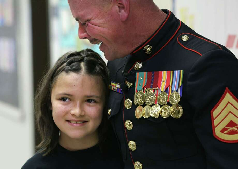 Marine Staff Sgt. Shannon Trotter smiles as he hold his smiling daughter, Alexis Trotter, after he surprised her in her fifth grade class at Wilderness Oak Elementary School on Thursday, May 30, 2013. Photo: Bob Owen, San Antonio Express-News / © 2012 San Antonio Express-News