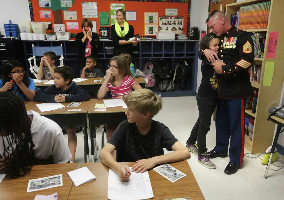 Marine Staff Sgt. Shannon Trotter back home from Afghanistan, embraces his daughter Alexis Trotter surprising her in her fifth grade class at Wilderness Oak Elementary School on Thursday, May 30, 2013. Photo: Bob Owen, San Antonio Express-News / © 2012 San Antonio Express-News