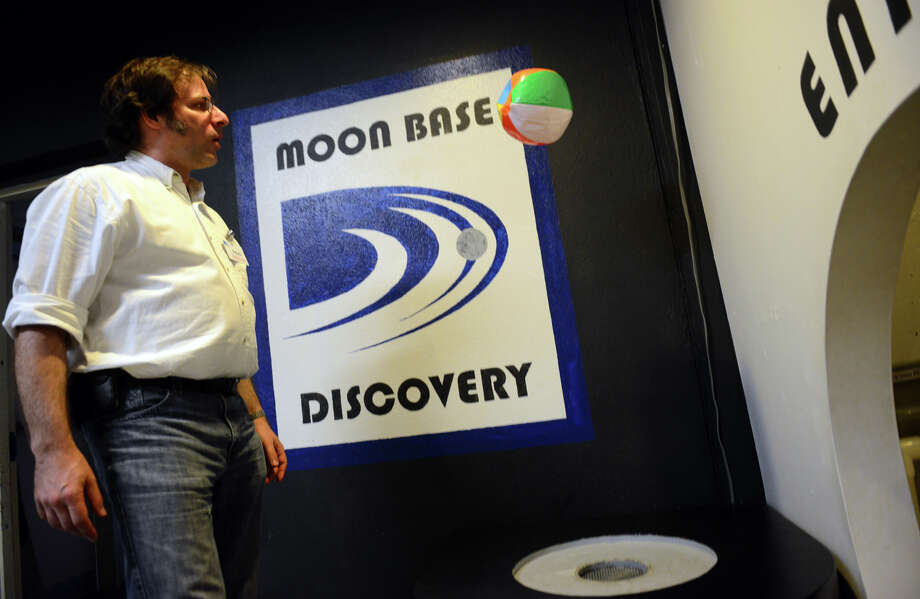 Adam Zuckerman, director of exhibits and public programs, shows off one of the features of the Moon Base Discovery exhibit at the Discovery Museum in Bridgeport, Conn. on Friday May 24, 2013. The museum is one of many attractions and institutions across the state participating in Open House Day 2013 on June 8. From 10 a.m. until 5 p.m., that day visitors receive half price off general admission. For more information, visit http://www.ctvisit.com. Photo: Christian Abraham / Connecticut Post