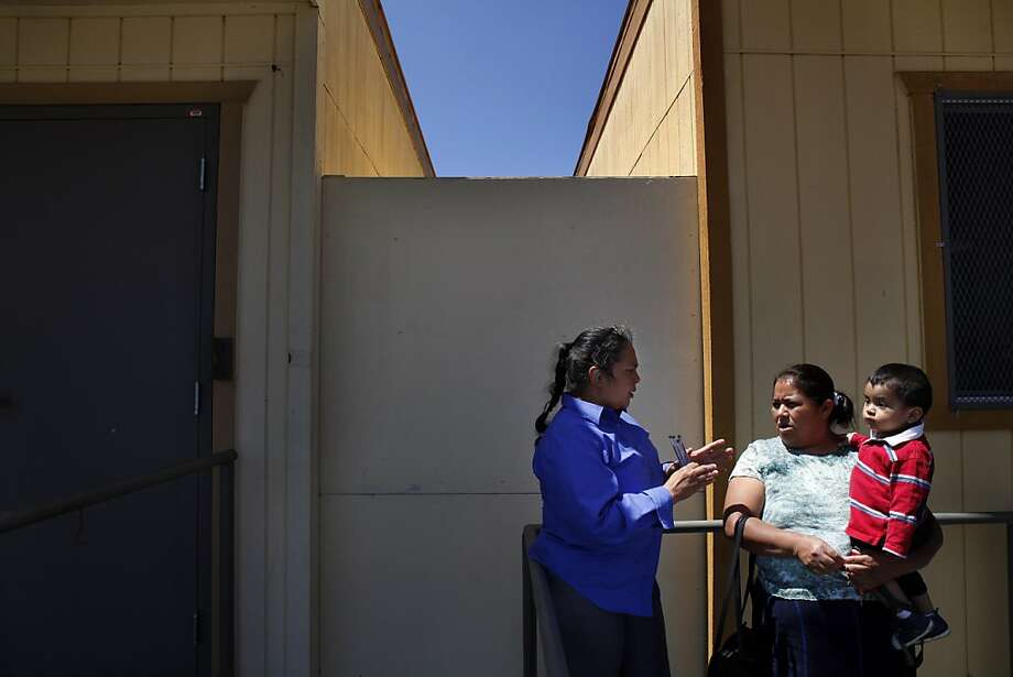 Jacqueline Portillo (left) speaks to Victorina Calmo about serving as a volunteer to inform people about health care changes. Photo: Carlos Avila Gonzalez, The Chronicle