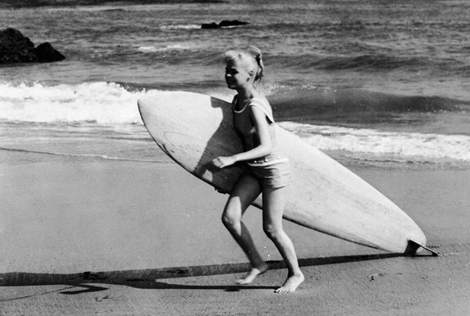 With a surfboard on the beach, 1959. Photo: Columbia Pictures, Getty