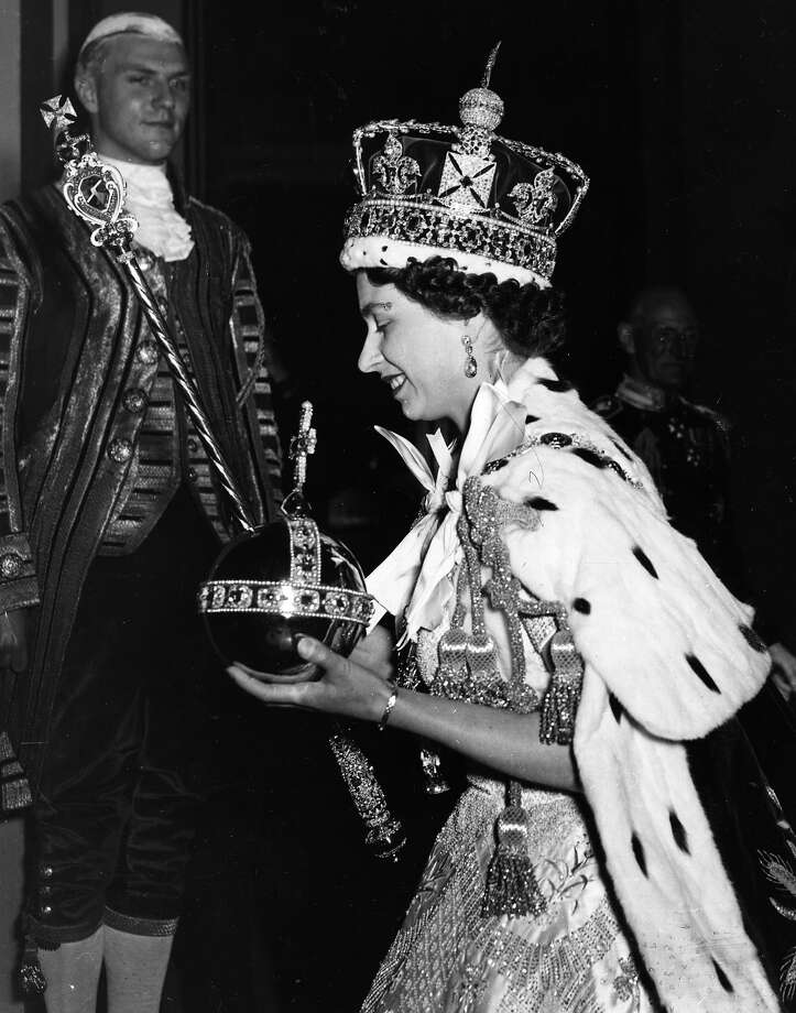 Queen Elizabeth II wearing the Imperial state Crown and carrying the Orb and sceptre, leaving the state coach and entering Buckingham Palace, after  the coronation.  Original Publication: Picture Post - 6537 - The Coronation Of Queen Elizabeth II - pub. 1953 Photo: Hulton Archive, Getty Images / Hulton Royals Collection