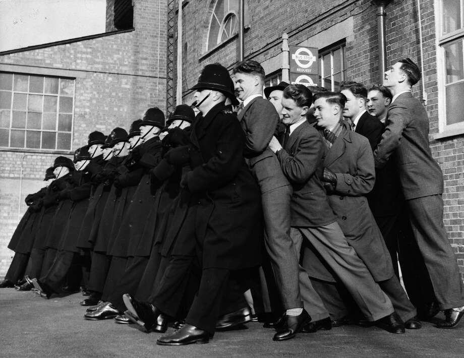A line of police constables in training for the enormous crowds expected at Queen Elizabeth II's Coronation, practising the 'linked arms' method of taking the pressure of a surging crowd, at the Police Training Centre in Hendon. Photo: Arthur Tanner, Getty Images / Hulton Royals Collection
