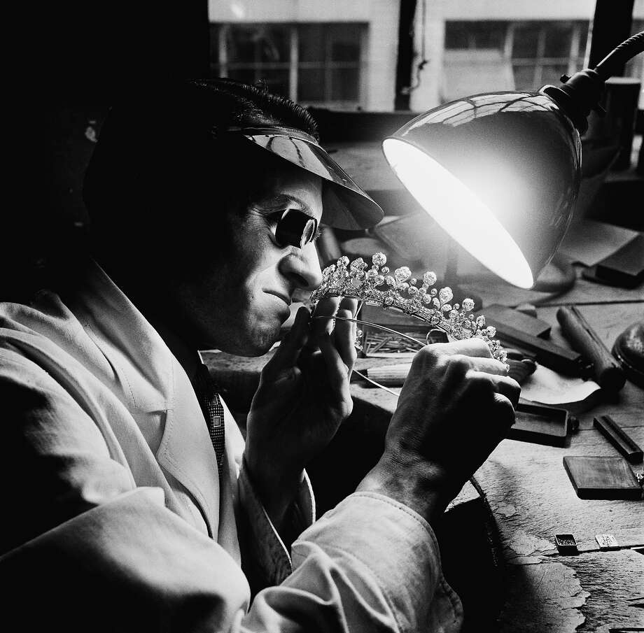 A diamond-setter examines a tiara at the Goldsmiths and Silversmiths Company Limited in Regent Street, London, before the Coronation of Queen Elizabeth II, 1953. Photo: Paul Popper/Popperfoto, Popperfoto/Getty Images / 2012 Popperfoto