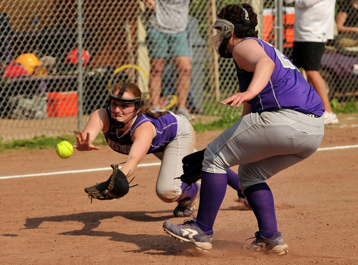Westhill third baseman Tammy Wise dives unsuccessfully for the ball as Sadie Apfel, right, looks on during their second round Class LL state softball championship game against West Haven at Westhill High School in Stamford on Thursday, May 30, 2013. West Haven won, 5-0.