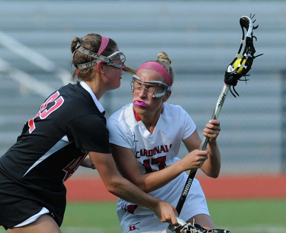 At right, Sophie Waine (# 17) of Greenwich advances the ball against Michelle Federico of Cheshire during the Class L girls lacrosse quarterfinal match between Greenwich High School and Cheshire High School at Greenwich, Thursday, May 30, 2013. Greenwich advanced to the next round as they defeated Cheshire, 19-9. Photo: Bob Luckey / Greenwich Time