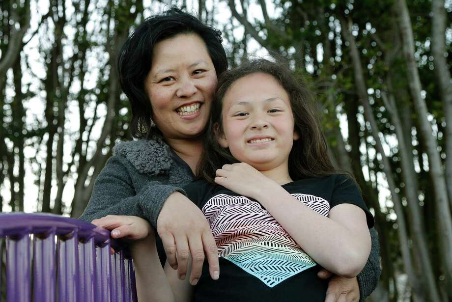 Joyce Chen hugs her daughter Kathryn, 10, as they pose for photographs in San Francisco, Wednesday, May 29, 2013. A new poll finds that one in five unmarried women would consider having a child on their own, and more than a third would consider adopting solo, just one indication of America's changing family structures. (AP Photo/Jeff Chiu) Photo: Jeff Chiu