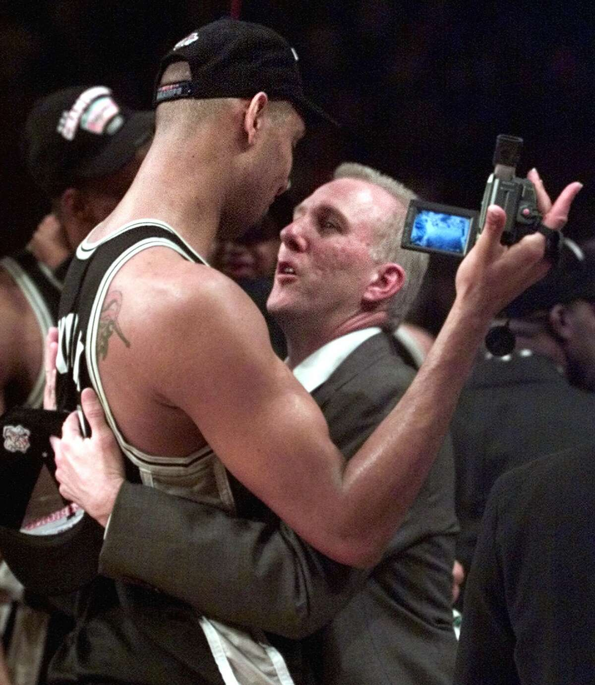 The Spurs' Tim Duncan (left) and coach Gregg Popovich celebrate after defeating the New York Knicks 78-77 to clinch the championship in Game 5 of the 1999 NBA Finals on June 25, 1999, at New York's Madison Square Garden.