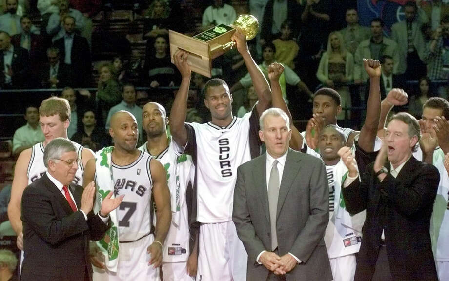 David Robinson holds up the McDonald's Championship trophy after the Spurs defeated Brazil Vasco Da Gama 103-68 to win the international tournament in Milan, Italy on Oct. 16, 1999. Celebrating with the team is NBA commissioner David Stern (left), coach Gregg Popovich and team owner Peter Holt (right). Photo: DOUG SEHRES, SAN ANTONIO EXPRESS-NEWS / SAN ANTONIO EXPRESS-NEWS