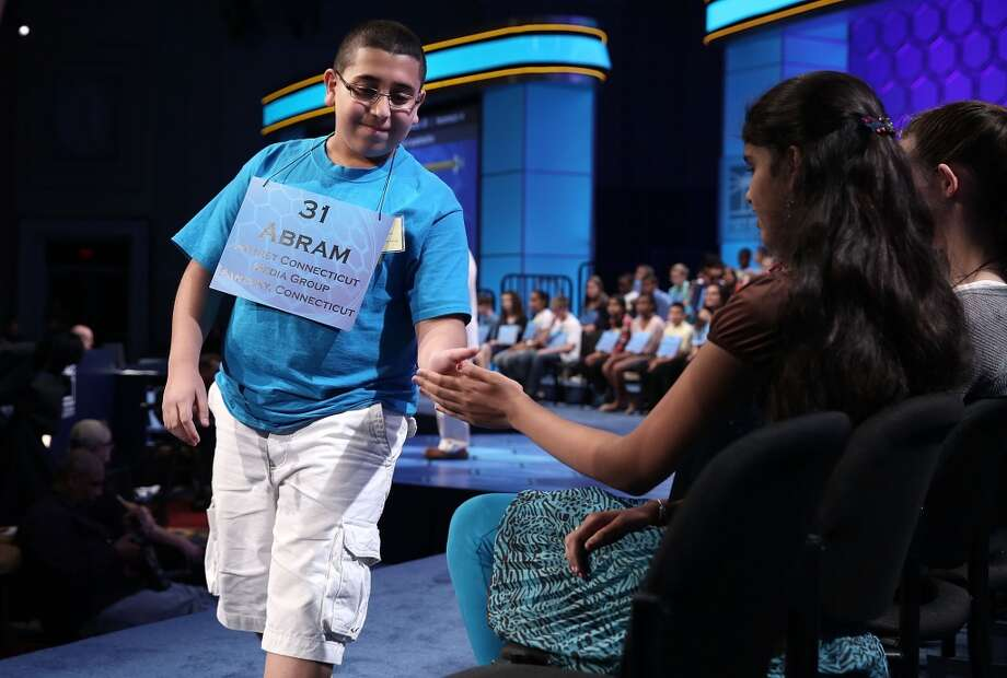"NATIONAL HARBOR, MD - MAY 29:  Abram Mikhaeel Goda (L) of Bridgeport, Connecticut, hi fives with Himanvi Kopuri (R) of Denver, Colorado, after he correctly spelled the word ""nomenclative"" in the round three of the 2013 Scripps National Spelling Bee May 29, 2013 at Gaylord National Resort and Convention Center in National Harbor, Maryland. Spellers competed in the annual spelling contest for the championship.  (Photo by Alex Wong/Getty Images)"