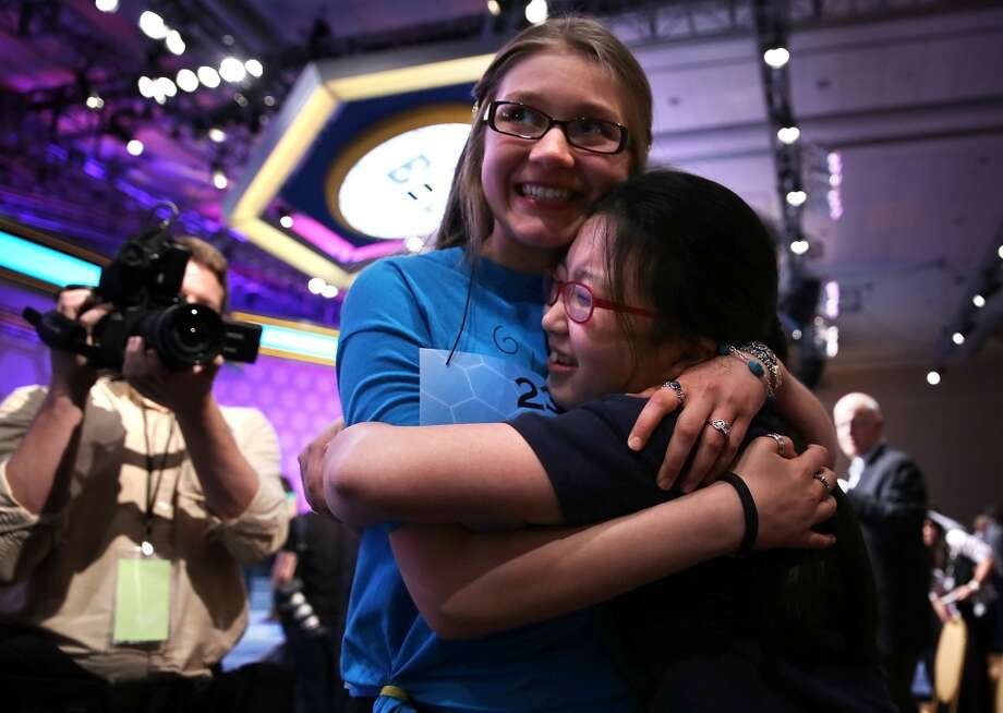 NATIONAL HARBOR, MD - MAY 29:  Katharine Wang (R) of Beijing, China, celebrates with Kate Miller (2nd R) of Abilene, Texas, after Wang found out she was advanced to semifinal the 2013 Scripps National Spelling Bee May 29, 2013 at Gaylord National Resort and Convention Center in National Harbor, Maryland. Spellers competed in the annual spelling contest for the championship.  (Photo by Alex Wong/Getty Images)