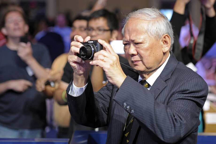 Dr. Ed Low, professor emeritus of English, Metropolitan State University of Denver, takes photos during the second round of the  Scripps National Spelling Bee in Oxon Hill, Md., Wednesday, May 29, 2013. (AP Photo/Cliff Owen)