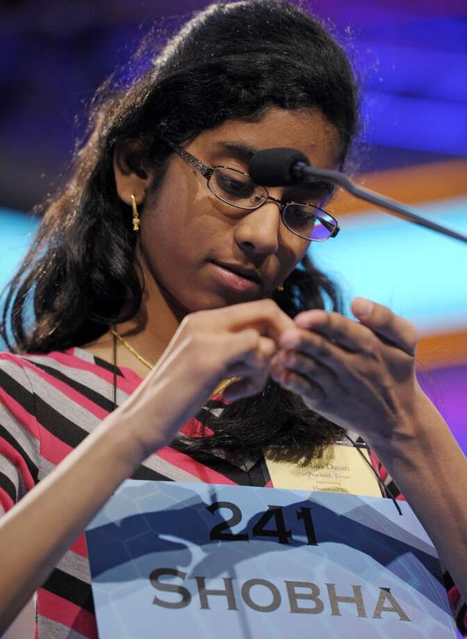 Shobha Dasari, 12, of Pearland, Texas spells her word with her finger during the second round of the Scripps National Spelling Bee in Oxon Hill, Md., Wednesday, May 29, 2013. (AP Photo/Cliff Owen)a