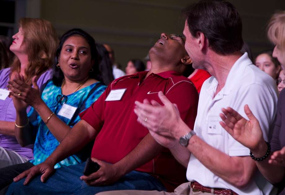 """Nadar Chandran reacts after his daughter Nikitha Chandran, 13, of Valrico, Fla., spells the word """"peristalith"""" correctly during the semifinal round of the National Spelling Bee, Thursday, May 30, 2013, in Oxon Hill, Md. At left is Sumita Chandran, Nikitha's mother. (AP Photo/Evan Vucci)"""
