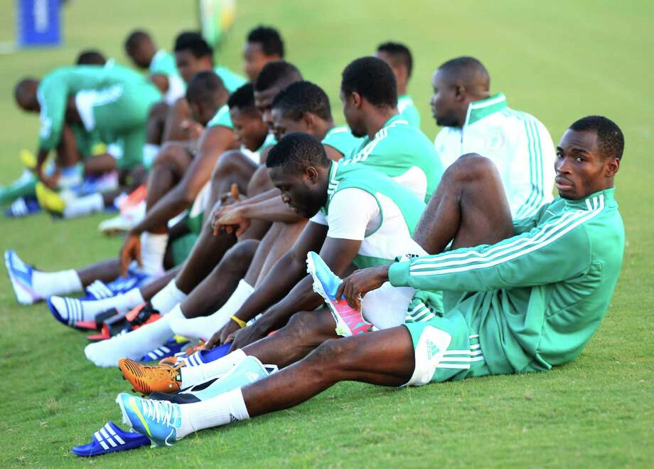 Benezer Odunlami, a member of the Nigeria National Team, puts on his shoes with his teammates before soccer practice at the Houston Amateur Sports Park, Wednesday, May 29, 2013, in Houston, as they prepare for Friday's game against Mexico National. Photo: Karen Warren, Houston Chronicle / © 2013 Houston Chronicle