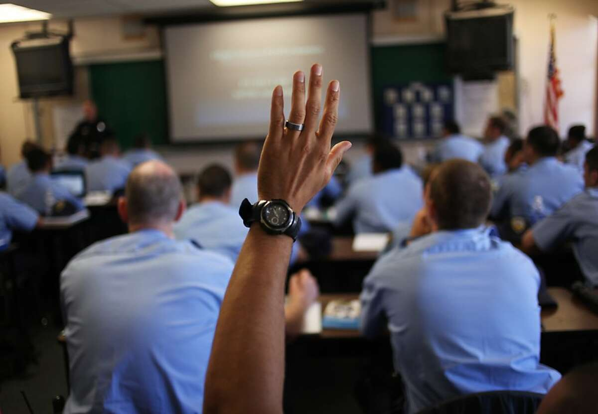 A recruit officer asks a question during announcements in a class room at the San Francisco Law Enforcement Regional Training Facility on Amber Street on May 30, 2013 in San Francisco, Calif.