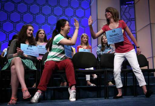 Isabel Cholbi (R) of San Bernardina, California, celebrates with Katharine Wang (2nd R) of Beijing, China, after she correctly spelled her word in the round five of the 2013 Scripps National Spelling Bee May 30, 2013 at Gaylord National Resort and Convention Center in National Harbor, Maryland. Forty-two have advanced to the semifinal of the annual spelling contest for the championship. Photo: Alex Wong, Getty Images / 2013 Getty Images