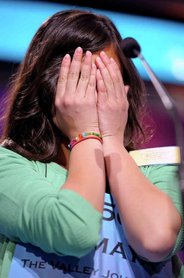 Vismaya Kharkar, 14, of Bountiful, Utah, covers her face while spelling her word during the finals of the Scripps National Spelling Bee in Oxon Hill, Md., Thursday, May 30, 2013. Photo: Cliff Owen, Associated Press / FR170079 AP