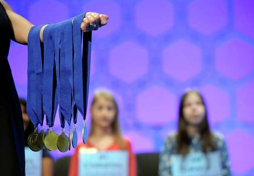 Janice Liebenberg, Sponsorship and Operations Coordinator, Scripps Spelling Bee, holds up the medals given to spellers advancing to the final round round of the Scripps National Spelling Bee in Oxon Hill, Md., Thursday, May 30, 2013. Photo: Cliff Owen, Associated Press / FR170079 AP