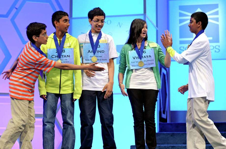 Sriram Hathwar, 13 of Painted Post, N.Y., left, reaches out to shake hands with Syamantak Payra, 12, of Friendswood, Texas, right, as he high-fives Vismaya Kharkar, 14, of Bountiful, Utah, as Chetan Reddy, 13 of Plano, Texas, yellow shirt, and Arvind Mahankali, 13, of Bayside Hills, N.Y., center, watch after they learned that they will advance to the final round of the Scripps National Spelling Bee in Oxon Hill, Md., Thursday, May 30, 2013. Photo: Cliff Owen, Associated Press / FR170079 AP