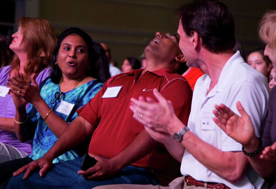 "Nadar Chandran reacts after his daughter Nikitha Chandran, 13, of Valrico, Fla., spells the word ""peristalith"" correctly during the semifinal round of the National Spelling Bee, Thursday, May 30, 2013, in Oxon Hill, Md. At left is Sumita Chandran, Nikitha's mother. Photo: Evan Vucci, Associated Press / AP"