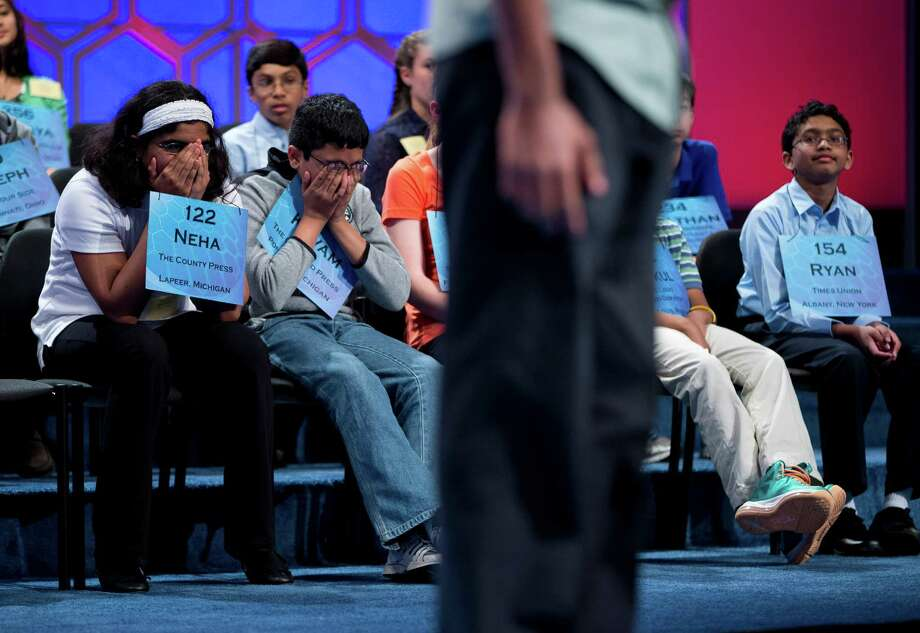 Neha Seshadri, 12, of Imlay City, Mich., left, Kuvam Shahane, 13, of Rochester Hills, Mich., center, and Ryan Devanandan, 13, of Albany, N.Y., right, listen as Anuk Dayaprema, 14, of Vincenza, Italy spells during the semifinal round of the National Spelling Bee, Thursday, May 30, 2013, in Oxon Hill, Md. Photo: Evan Vucci, Associated Press / AP