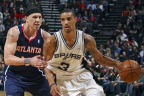 Spurs' George Hill drives around Hawks' Mike Bibby during first half action Friday Dec. 10, 2010 at the AT&T Center.