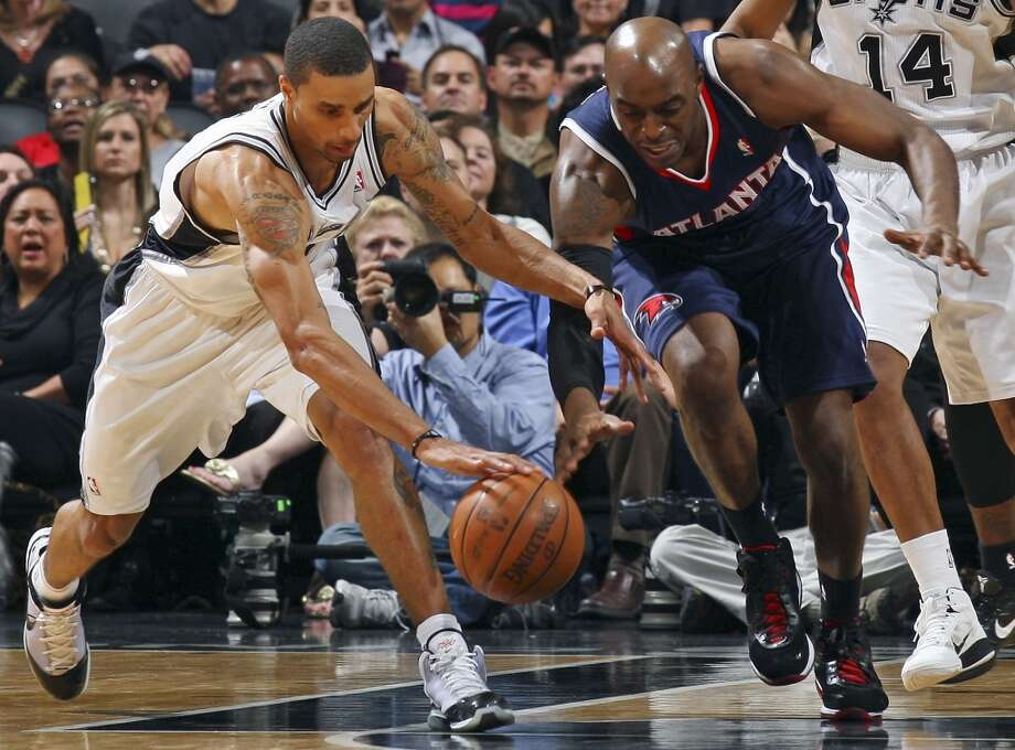 The Spurs' George Hill and Hawks' Damien Wilkins grab for a loose ball during second half action Friday Dec. 10, 2010 at the AT&T Center. The Spurs won 108-92. (PHOTO BY EDWARD A. ORNELAS/eaornelas@express-news.net)